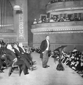 Booker T. Washington holds a Carnegie Hall audience spellbound, 1906.  Mark Twain is seated directly behind Mr. Washington, New York Times photograph, public domain image